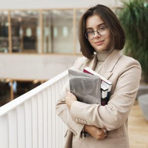 education business and women concept portrait of young attractive elegant female tutor young teacher or student carry studying books and laptop standing in hall smiling camera 300x300